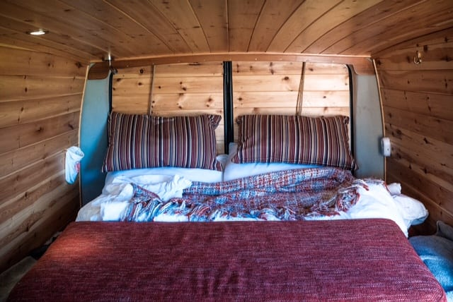 The bed inside of a Mercedes campervan converted into a quirky camper