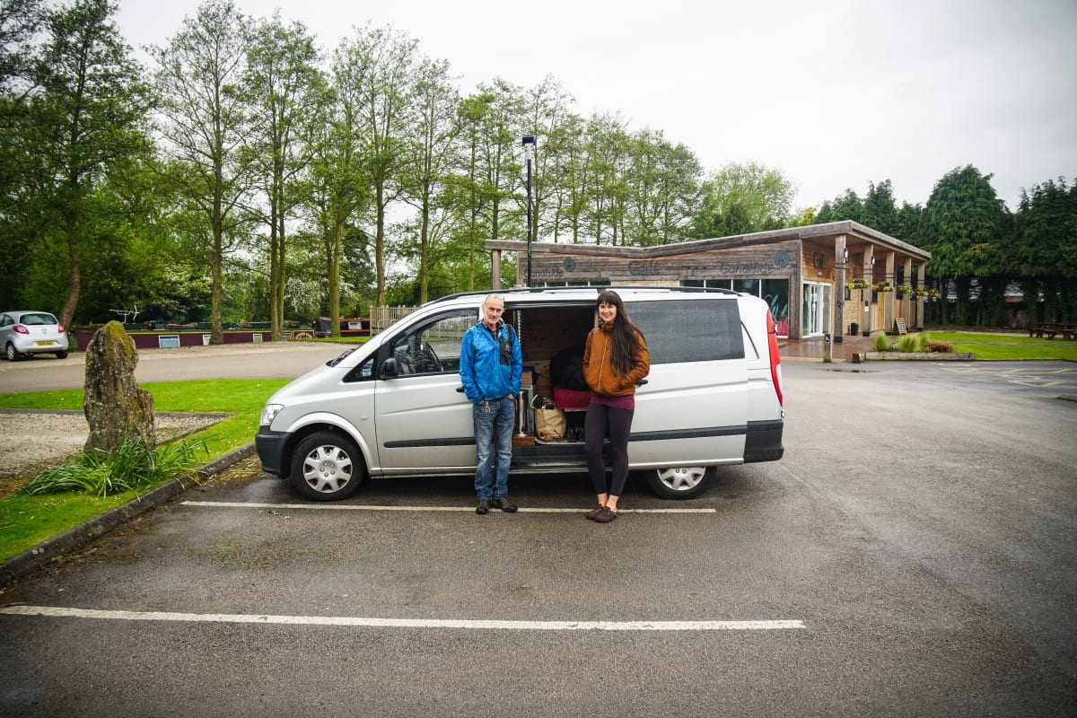 A man and woman stood by their campervan in an empty car park