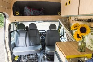 The inside of one of our quirky campervans showing storage and sunflowers