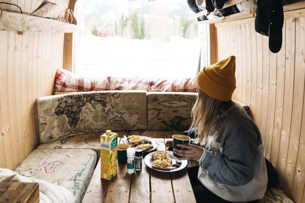 a woman having breakfast in a campervan