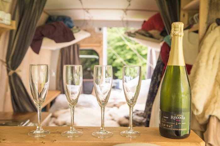 champagne and four flutes in a hire campervan at a wedding