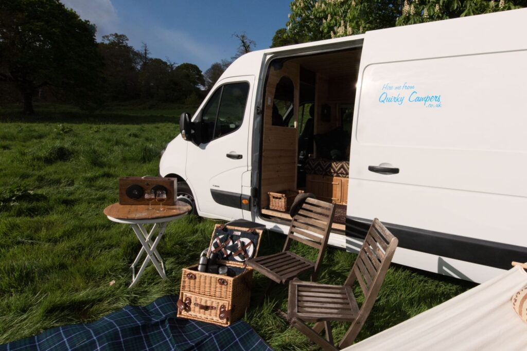 Outside of a campervan  with picnic bx, blanket and two chairs
