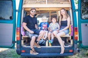 Family with two young children sit in the back of their self-built quirky campervan