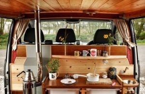 The inside of a selfbuilt campervan including diesel heater, mugs, saucepans and plants looking over into the front cab
