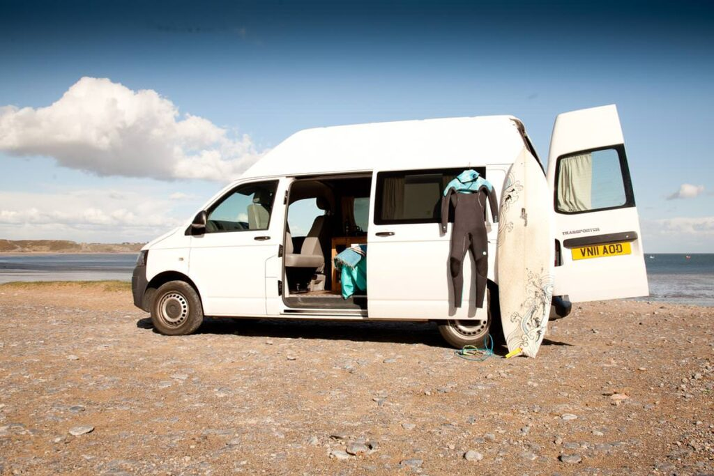 White campervan with wetsuit and surfboard on a beach