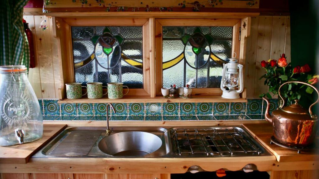 The kitchen of a citroen Relay conversion with stained glass and beautiful tiles and tea pot