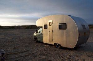 Sir James a handmade campervan available to rent on a beach as the sunsets
