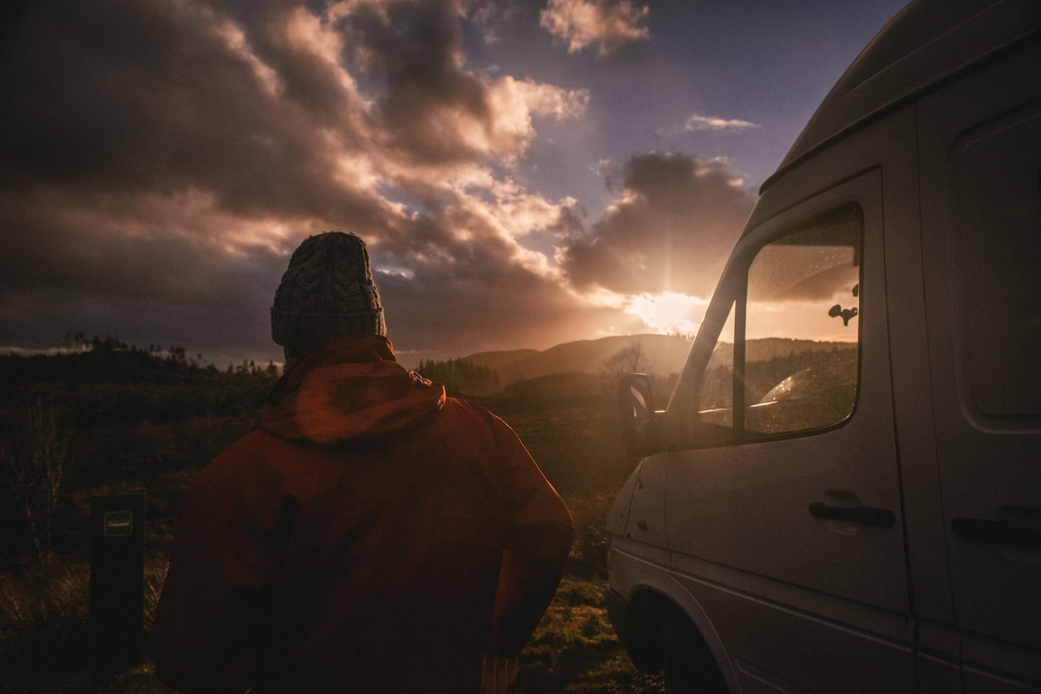 A man with his campervan as the sun sets
