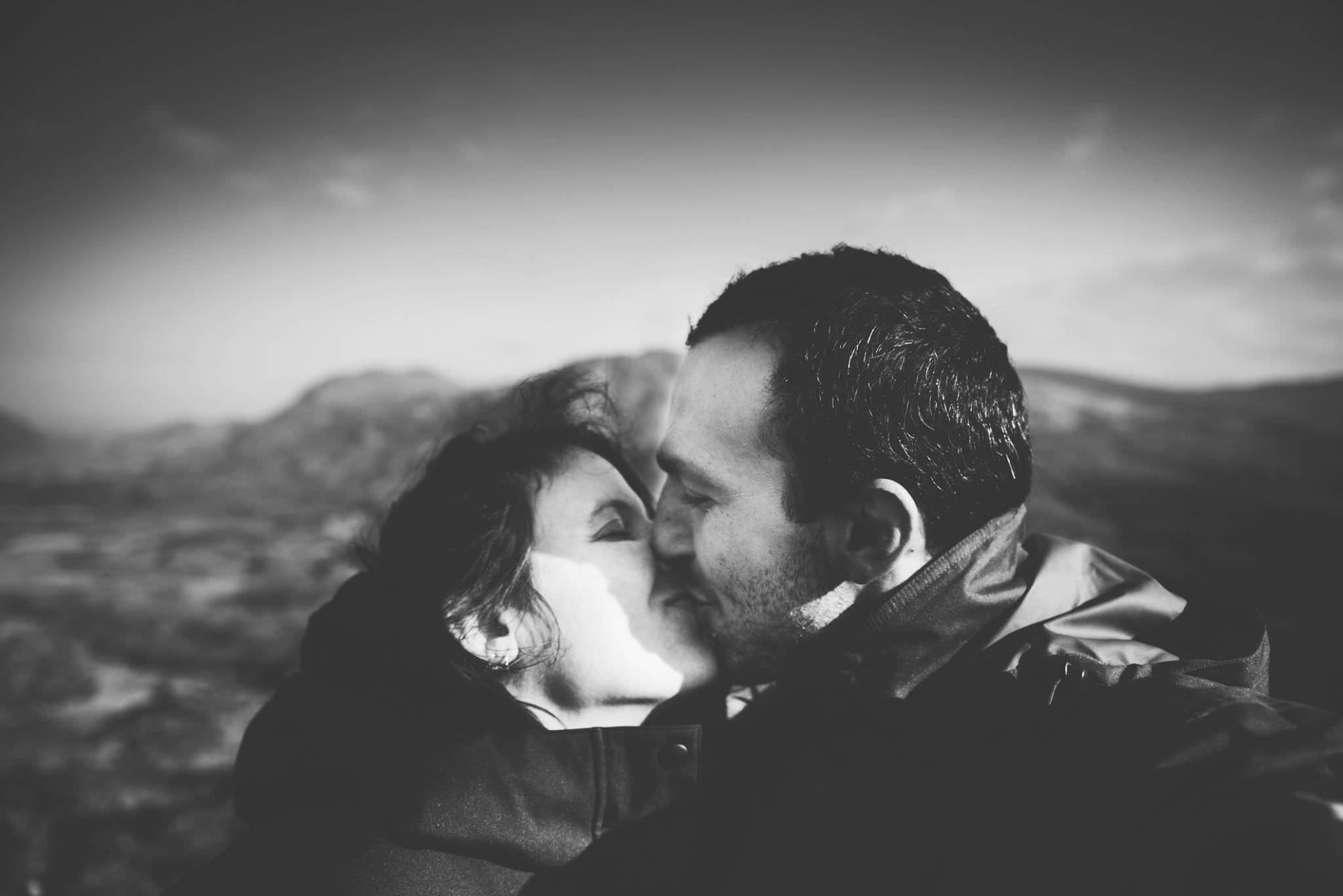 A man and a woman kissing whilst on a romantic campervan holiday in Ireland