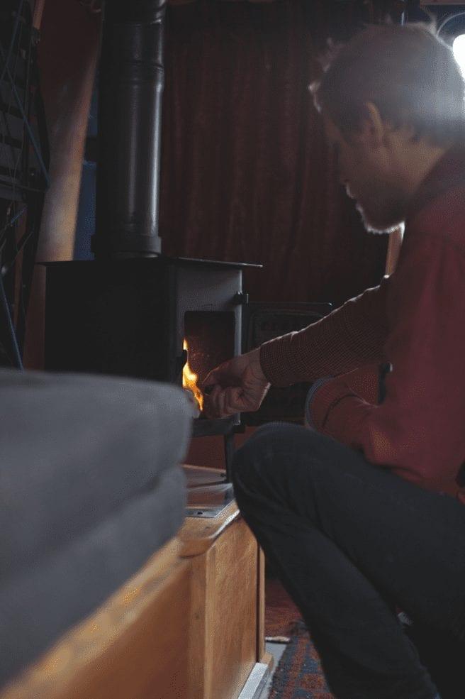 A man putting wood in a wood burner in a campervan