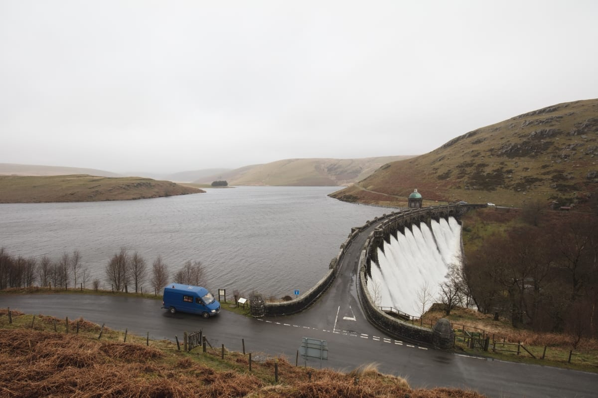A campervan by a dam in Wales