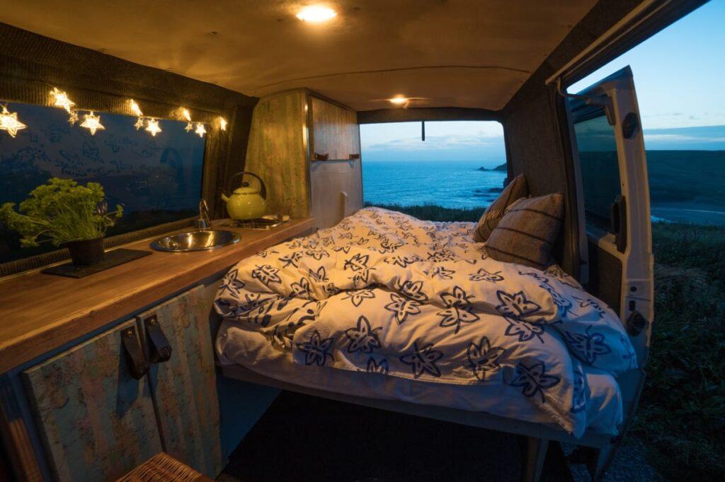 The bed area at night inside this handmade selfbuilt campervan. Hire him at https://www.quirkycampers.com/uk/campervans/devon/exeter-devon/baxter/
