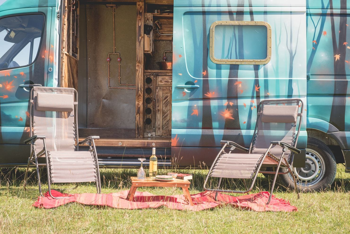 The outside of a campervan with two picnic chairs, wine and a picnic blanket