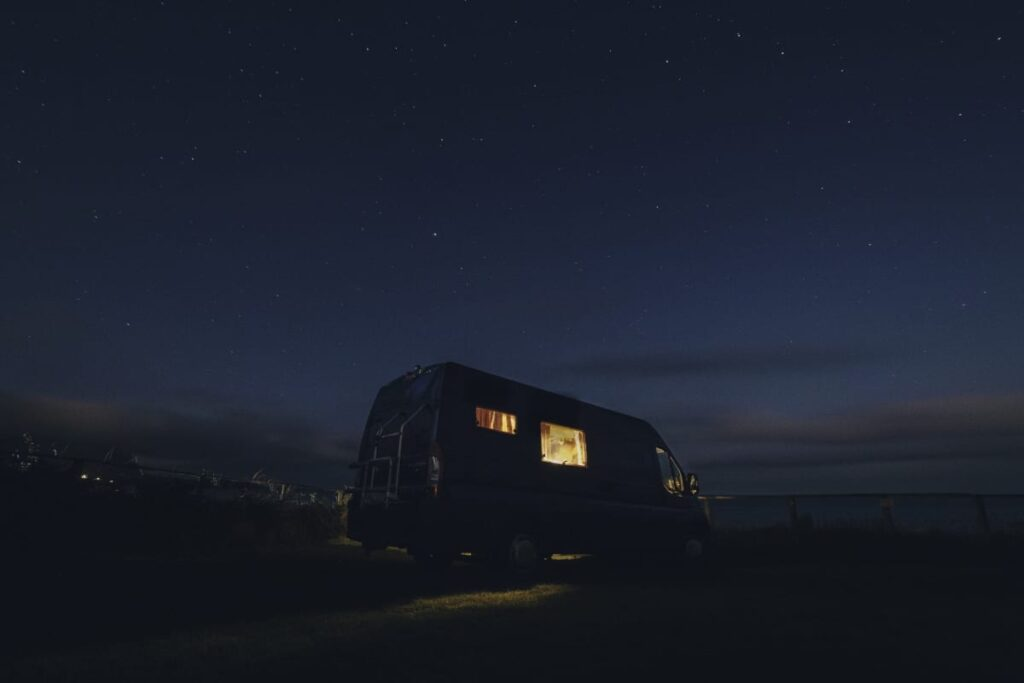 a campervan with its lights on in the darkness