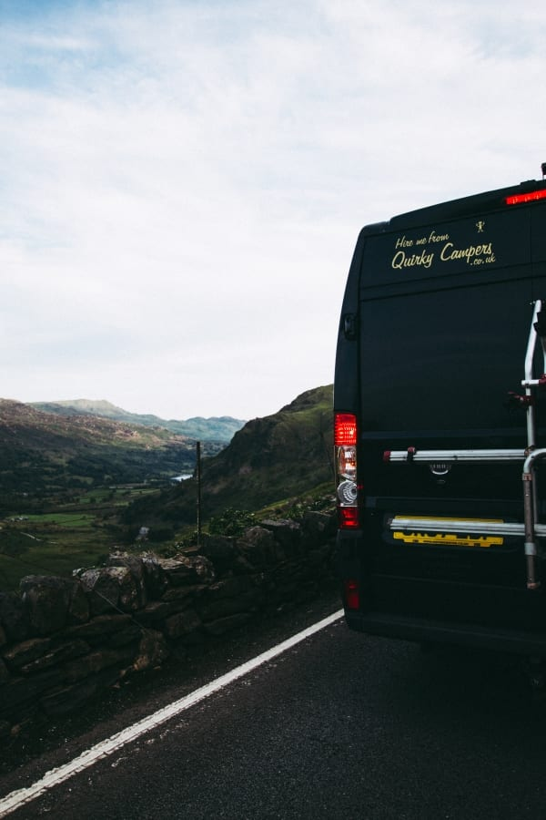 The back of a campervan overlooking the mountains in Wales