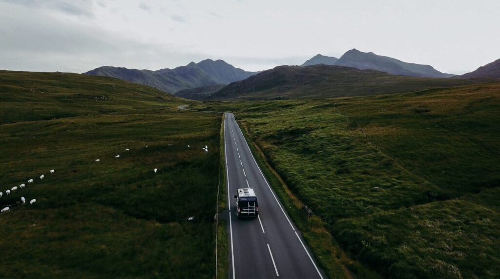 A campervan driving down a road in the mountains in Wales
