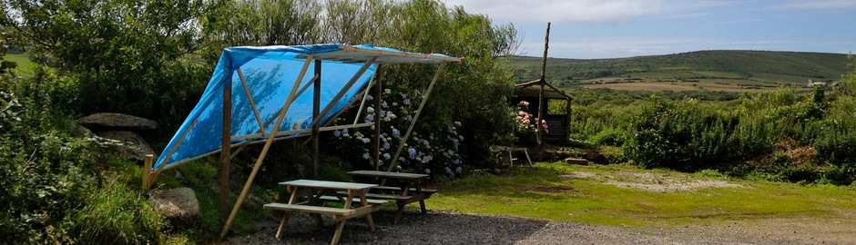 a campsite in cornwall with picnic tables