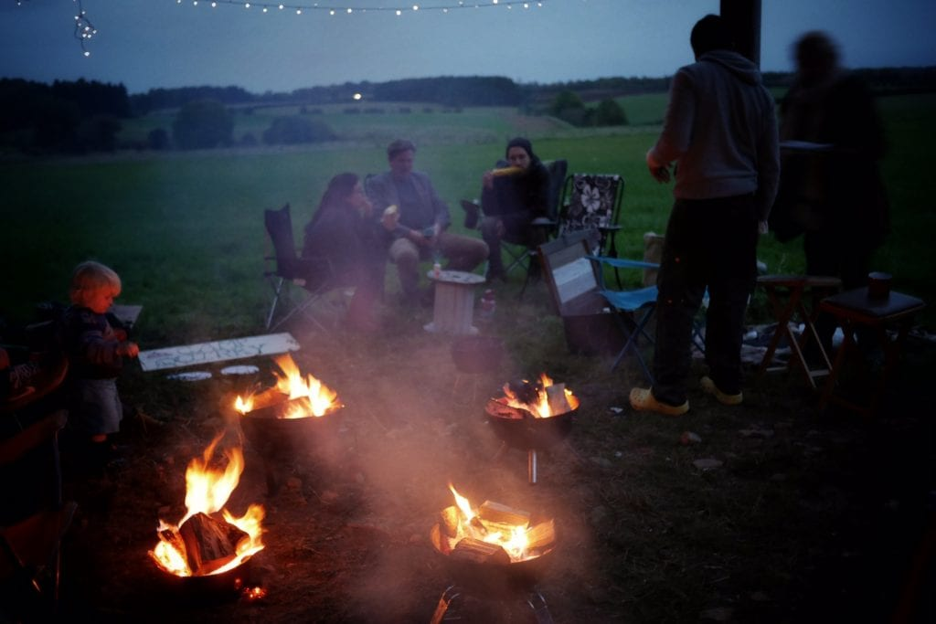 a group of people sat around campfires at a campervan festival