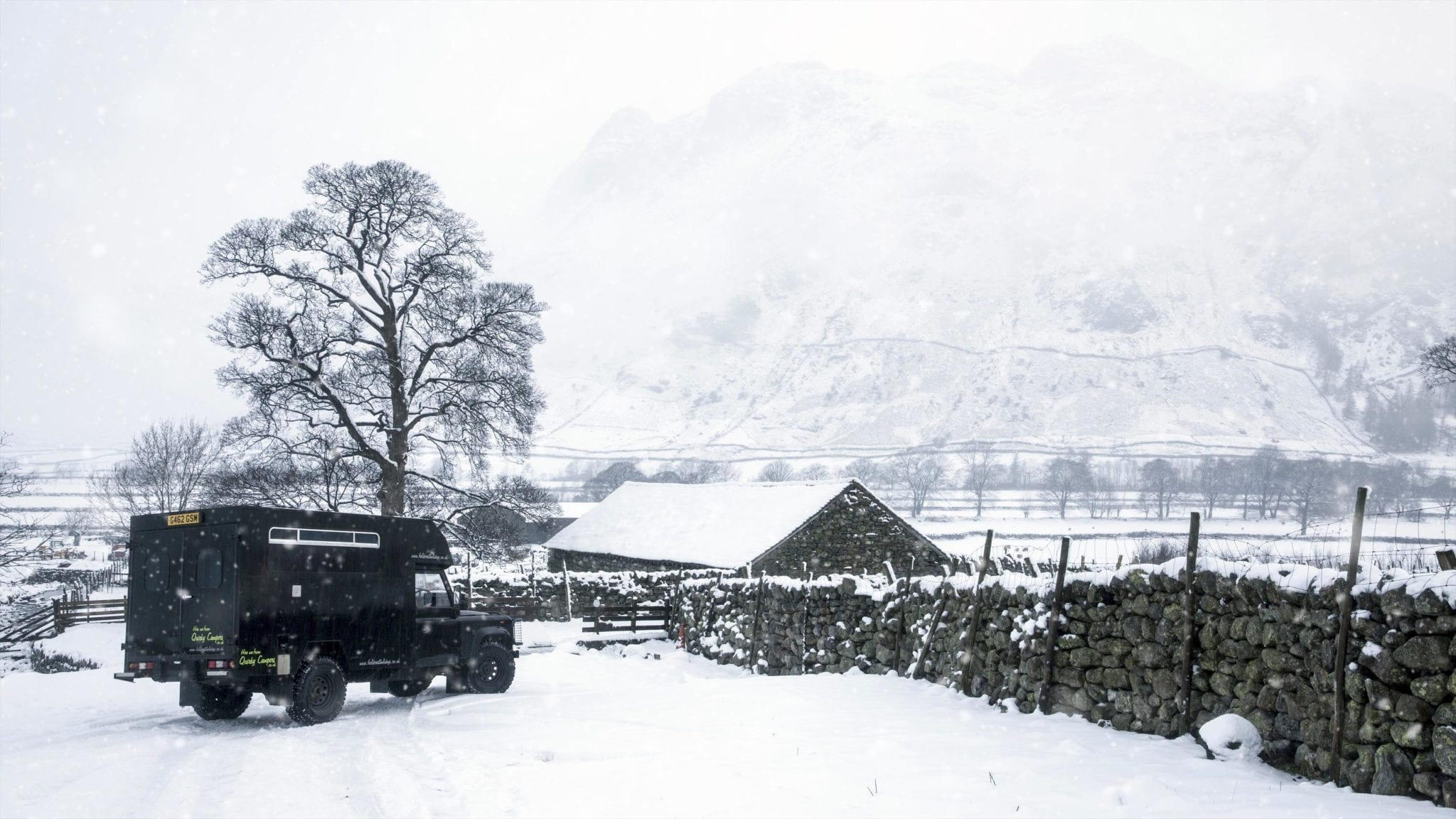 a campervan in the snowy british countryside on an adventure holiday in UK