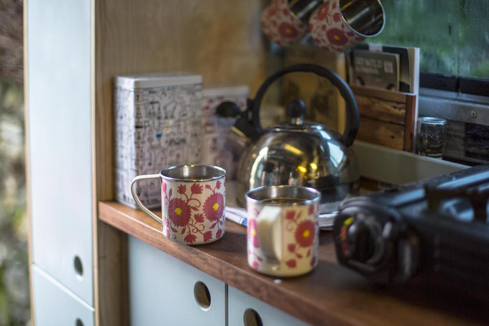 two mugs of coffee and a kettle in a campervan