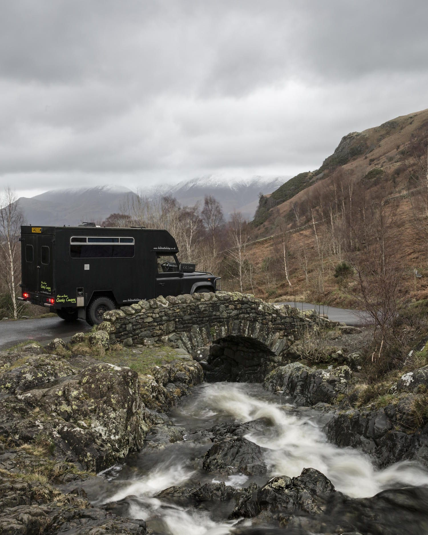 A campervan crossing a tiny stream bridge on an adventure holiday in UK