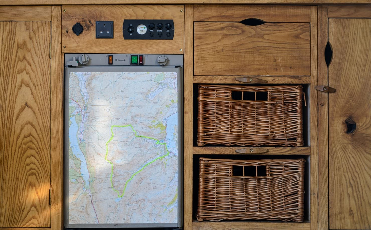 beautiful wooden campervan kitchen with fridge covered in a map