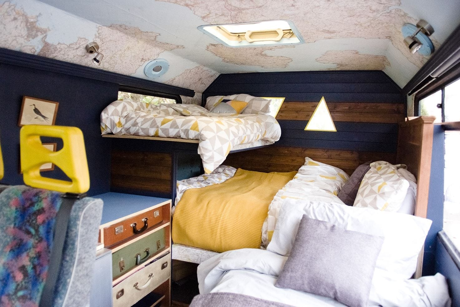 a converted selfbuilt campervan with a duble bed, single bed and maps on the ceiling