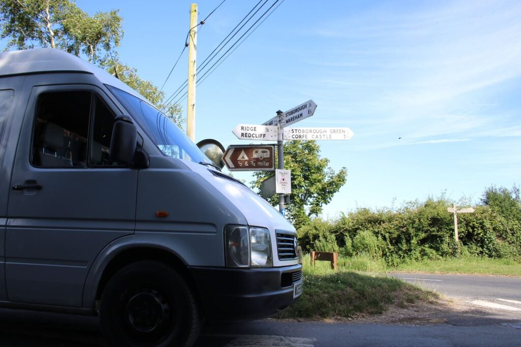 The front of a campervan at a crossroads on a country lane