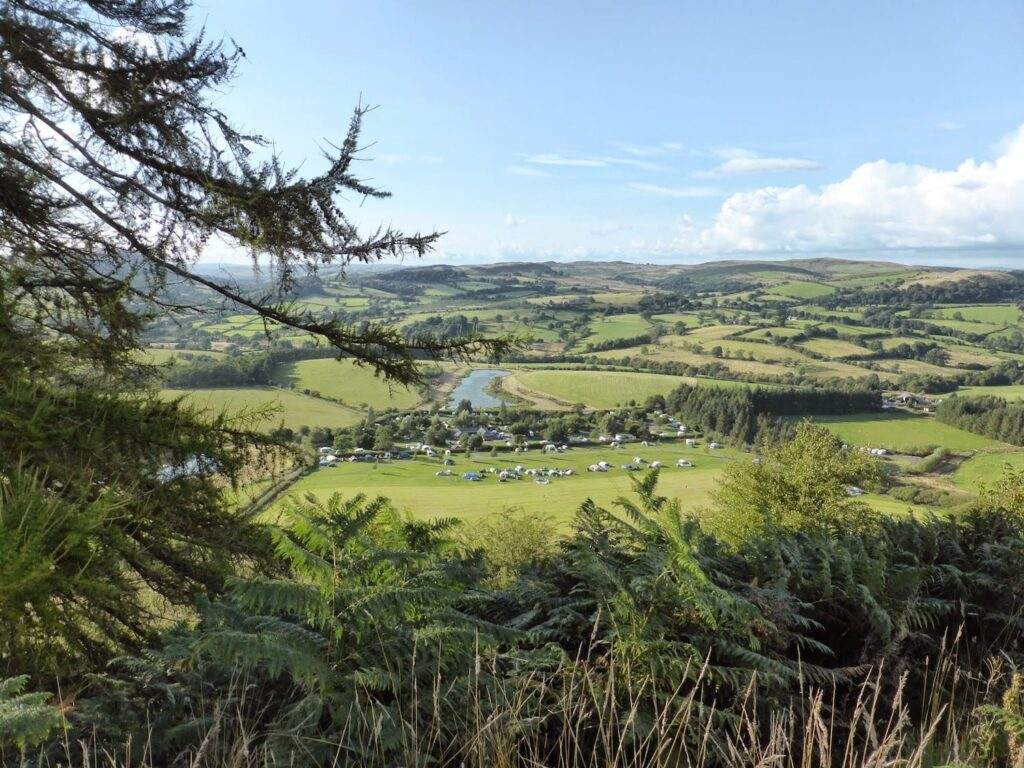 A view of fields and trees and a lake in mid wales