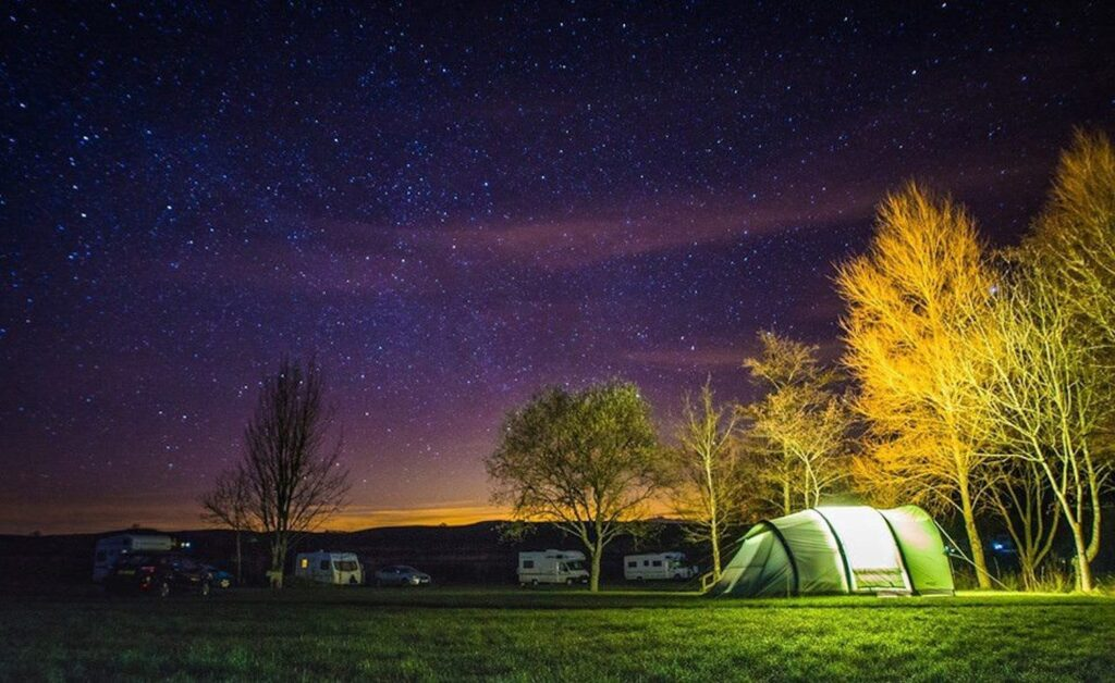 A starry night on a campsite with a tent and some campervans