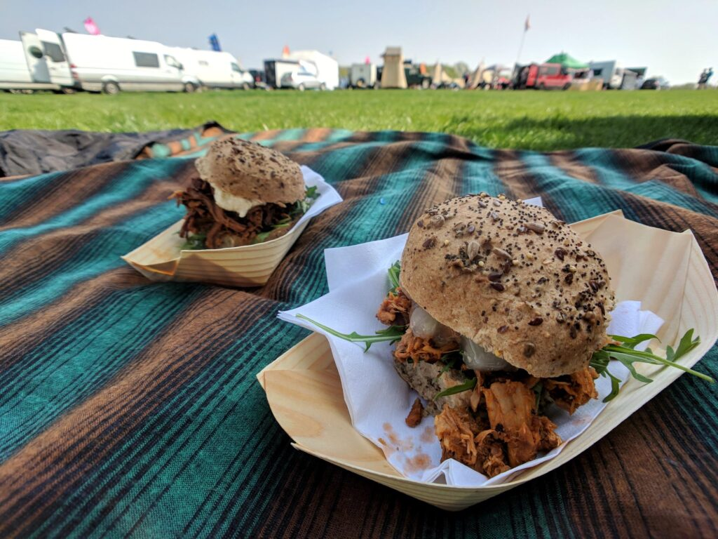 Two burgers on a picnic blanket in a campervan festival field