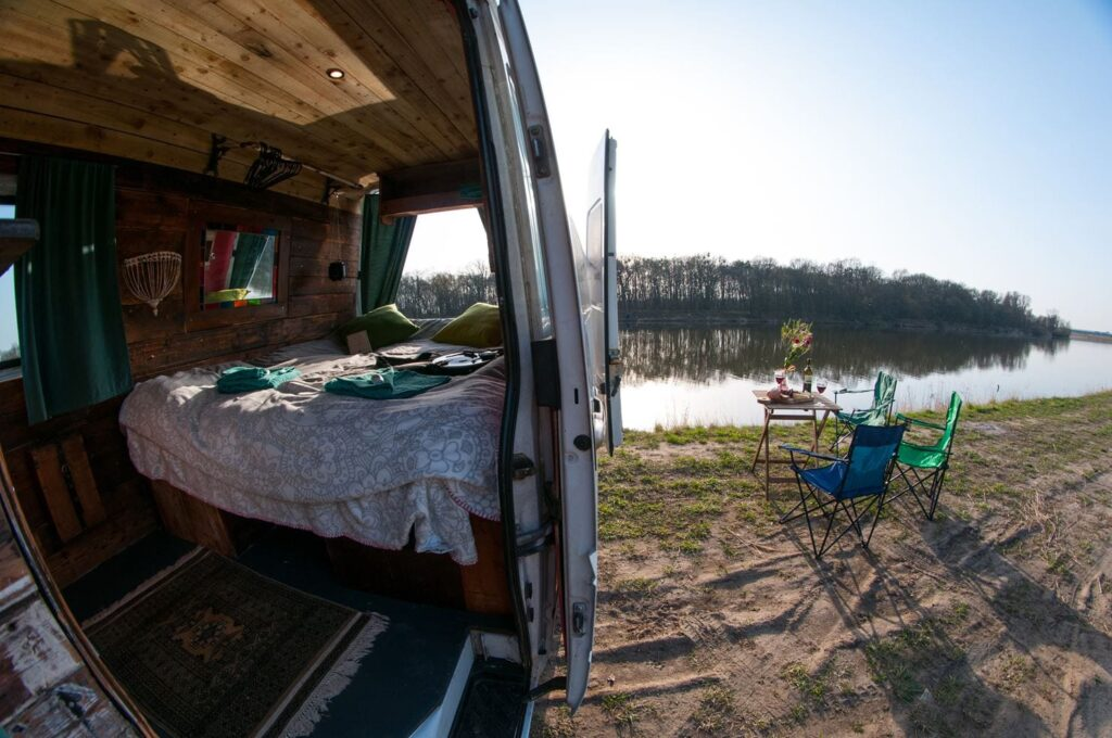 the bed and inside of a campervan looking out onto a lake