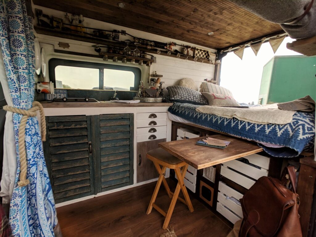 The inside of a handmade campervan including bed, dining and kitchen area