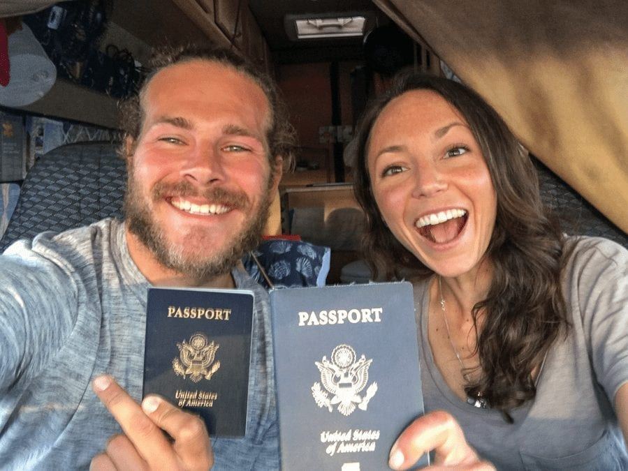 American couple traveling the UK in a campervan with their passports and smiles