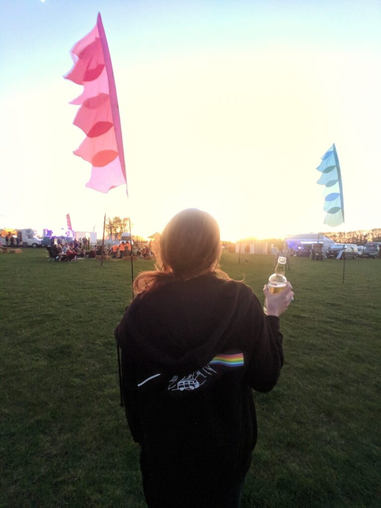 A woman walking in a festival field with festival flags in the background