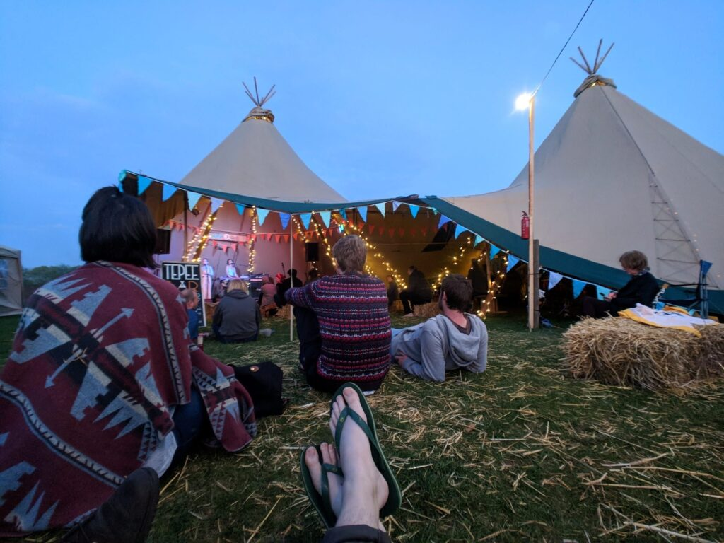 The Camp Quirky teepee with people sat outside and hay bales