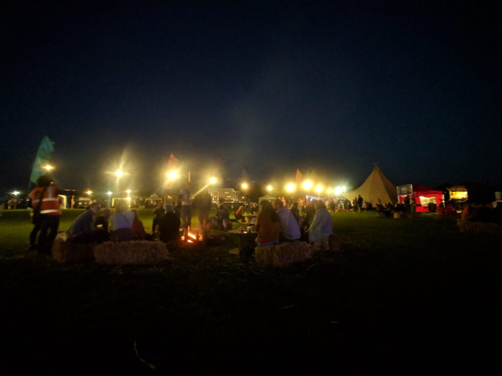 Sitting around a campfire at Camp Quirky, the UK's first selfbuilt campervan festival