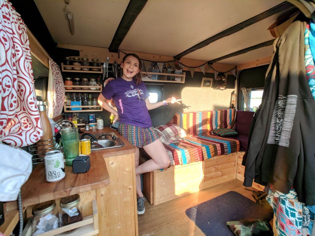 A woman showing off the inside of her selfbuilt campervan living area