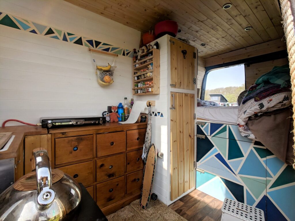 The inside of a selfbuilt campervan with a lot of storage drawers