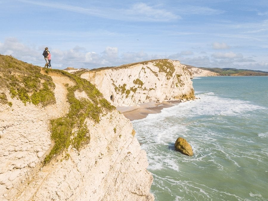 cliffs in the UK with the sea below and two americans looking into the distance