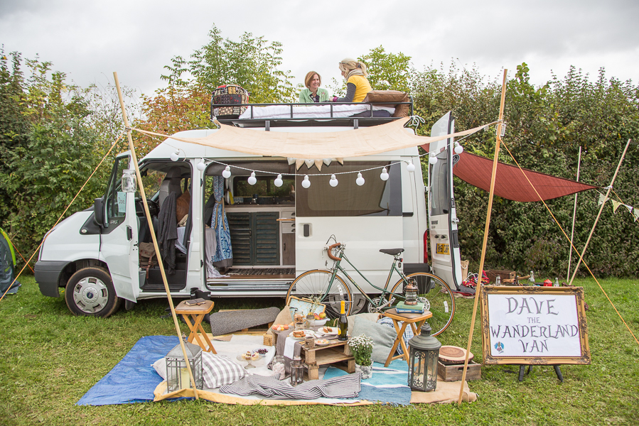 a converted ford transit campervan wih two people relaxing on the roof and rugs and chairs in front