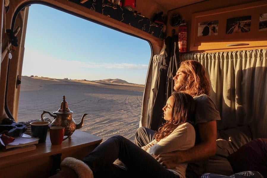 Couple cuddling looking into the Moroccan sand dunes with a Moroccan tea pot on the table