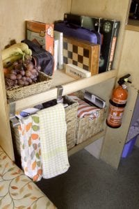 A cupboard in a selfbuilt camprevan that contains a fire extinguisher among other things such as bananas, grapes, tea towels, books, and a chess board