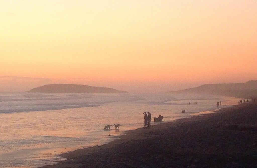 Sunset on a Welsh beach with a few people and some dogs