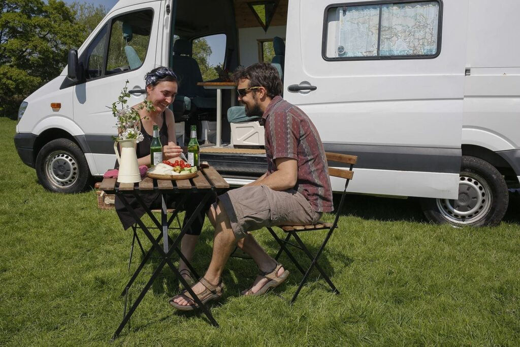 Man and woman sit outside their campervan at a picnic table