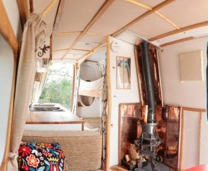 The inside of a selfbuilt campervan with a woodburner to heat the van