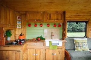 The inside of a selfbuilt campervan with gas hob, Belfast sink, 6 hanging mugs and the edge of a comfy sofa