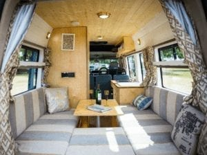 The inside of a selfbuilt campervan including sofas, table and soft furnishings