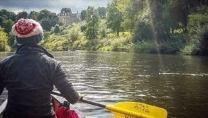 A woman in a bobble hat and coat canoeing down the Wye River