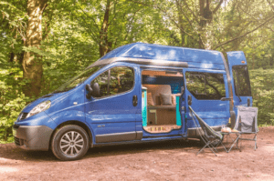 A blue campervan with two camp chairs parked in a wooded area